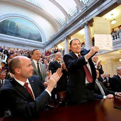 Gov. Gary Herbert holds up a copy of SB296 after signing it at the Capitol in Salt Lake City on Thursday, March 12, 2015.