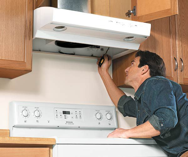 Contractor Looking Up Into A Basic Vent Hood In Kitchen