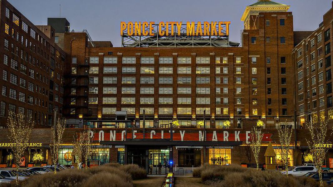 U-shaped multi-story building with Ponce City Market sign on roof and cyclists in front.