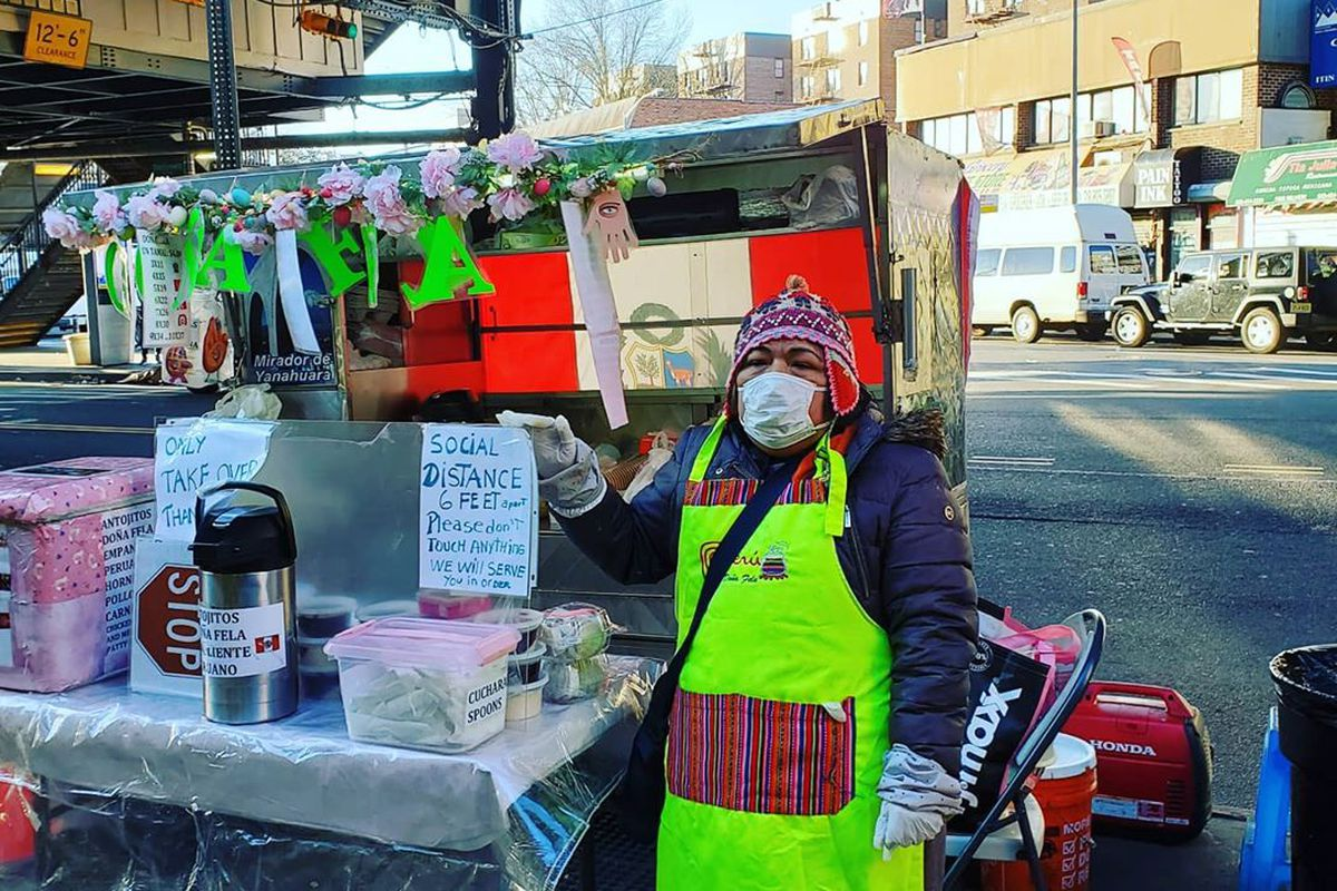 A woman wearing a mask and gloves is standing in front of a food cart on a street