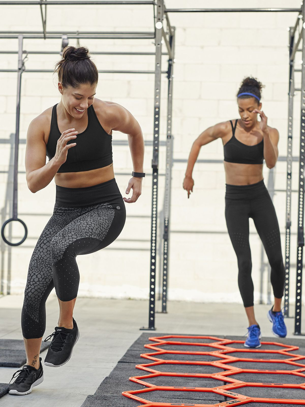 58b0bf746cdfb Two women working out in Athleta sports bras and leggings in the gym.