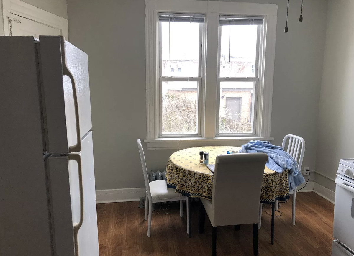 An image of a dining room table with three white chairs. There is a window and a refrigerator.