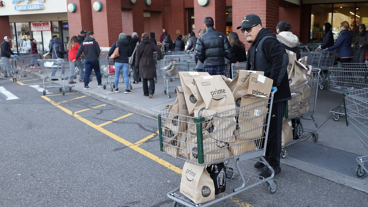 A worker leaves Whole Foods in Jericho, New York with Amazon Prime delivery packages stacked in a cart.
