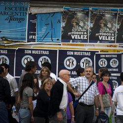 """People walk by a wall plastered with signs that read in Spanish """"They are ours. CFK. YPF. They are Argentine"""" in Buenos Aires, Argentina, Tuesday April 17, 2012.  President Cristina Fernandez pushed forward a bill to renationalize the country's largest oil company on Monday despite fierce criticism from abroad and the risk of a major rift with Spain. Fernandez said the legislation put to congress would give Argentina a majority stake in oil and gas company YPF by taking control of 51 percent of its shares currently held by Spain's Repsol."""