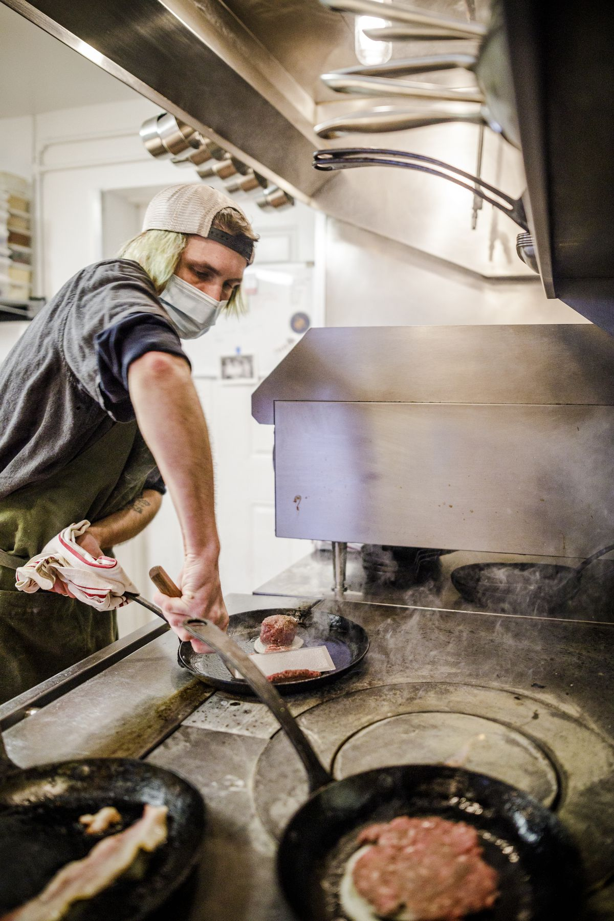 A man with blue-green hair smashes a beef patty into a sizzling cast iron plate
