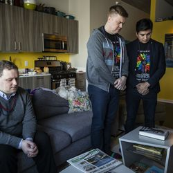 Matt Schreck, 43, his husband, Fernando Gutierrez, 41, and their friend Brian Dowling, 39, bow their heads during a moment of silence for COVID-19 victims during the inauguration ceremony for President Joe Biden and Vice President Kamala Harris at Schreck and Gutierrez's South Loop home, Wednesday morning, Jan. 20, 2021.