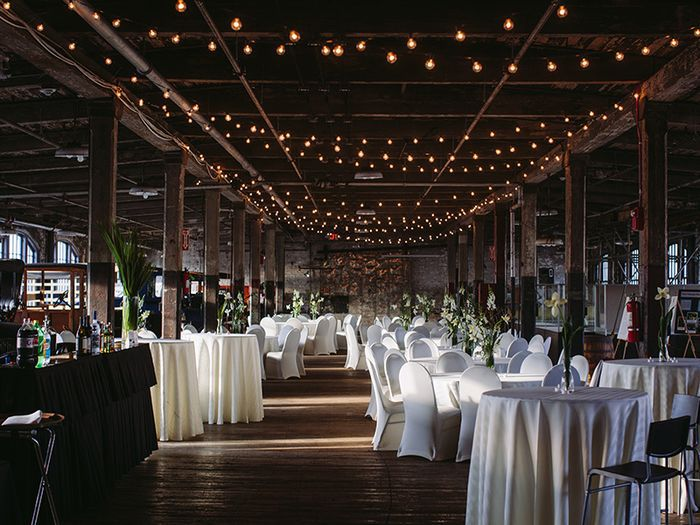 The interior of the Ford Piquette Avenue Plant. The room is decorated for a wedding with string lights hanging from the ceiling. There are many tables and chairs.