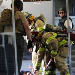 """Firefighters check a victim as officials conduct the terrorist attack protection and response drill """"Hell on Wheels"""" at the Salt Lake City Central station, the drill simulates multiple terrorists entering the Salt Lake Valley and dividing up on Tuesday, Aug. 8, 2017."""