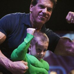 Xander Zufelt, center, shows off his muscles with Lou Ferrigno during the Salt Lake Comic Con kick off press conference at the Salt Palace Convention Center, Thursday, Sept. 4, 2014.