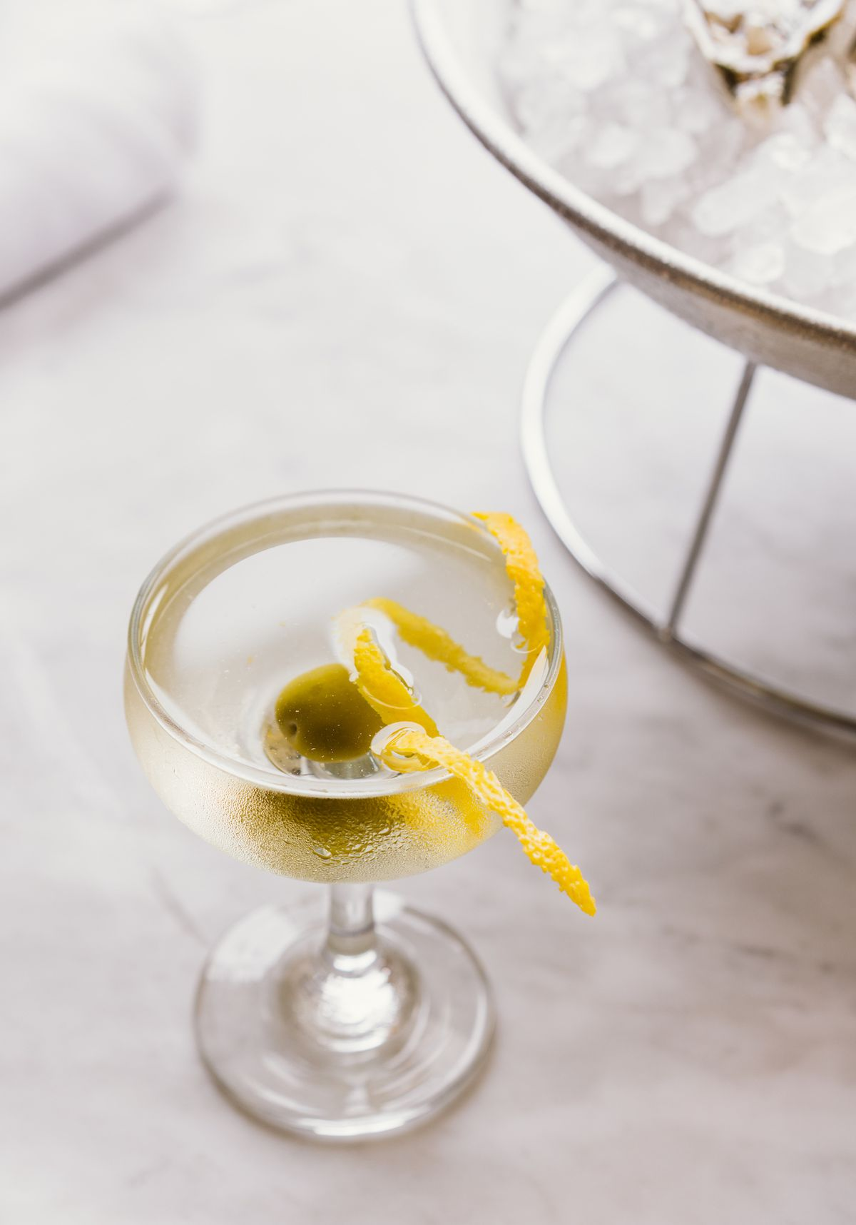 A clear alcohol cocktail with a lemon twist.