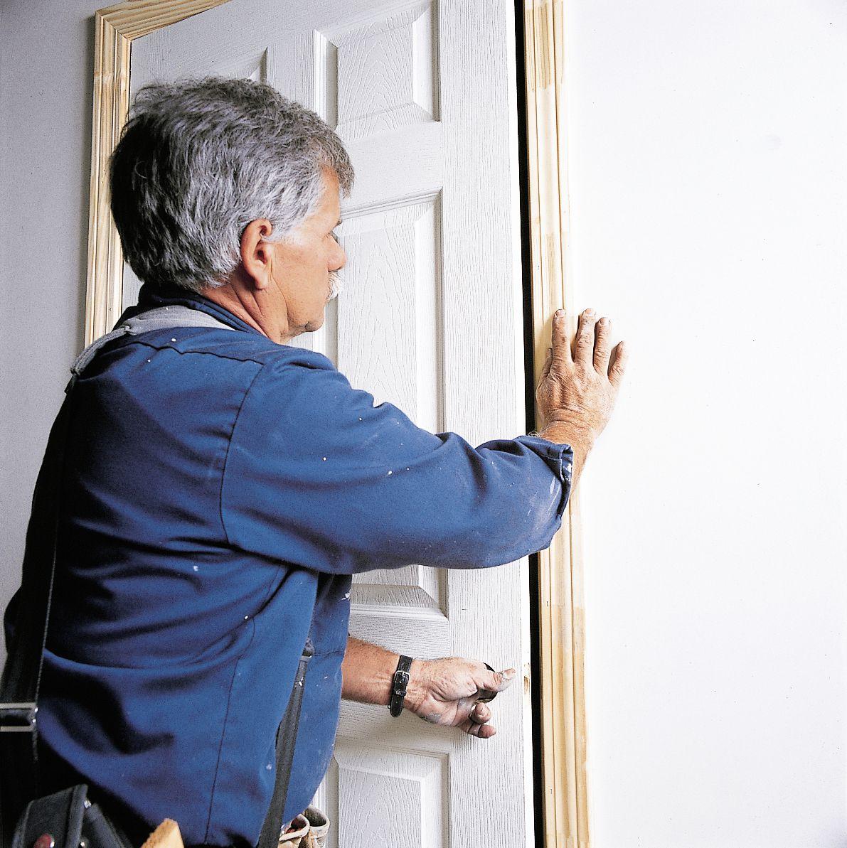 Man Checks Horizontal Gap Or Reveal Of Doorway