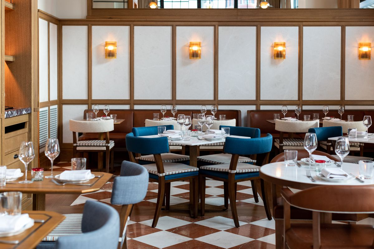 The empty dining room at San Morello has a mid-century interior with high ceilings, would accents, and blue, gray, and white chairs.