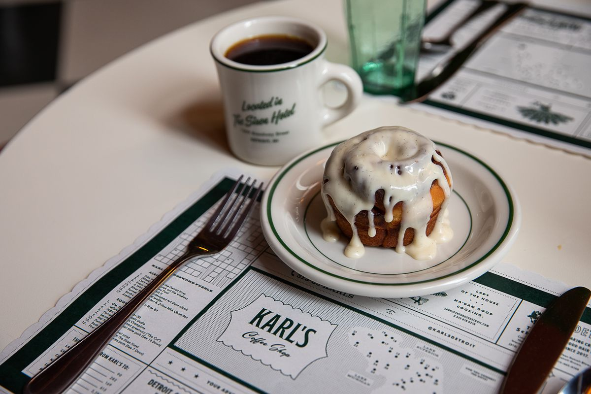 A cinnamon roll dripping with thick, white icing is sitting on a small green and white plate next to a branded coffee mug and on top of a Karl's Coffee Shop placemat.