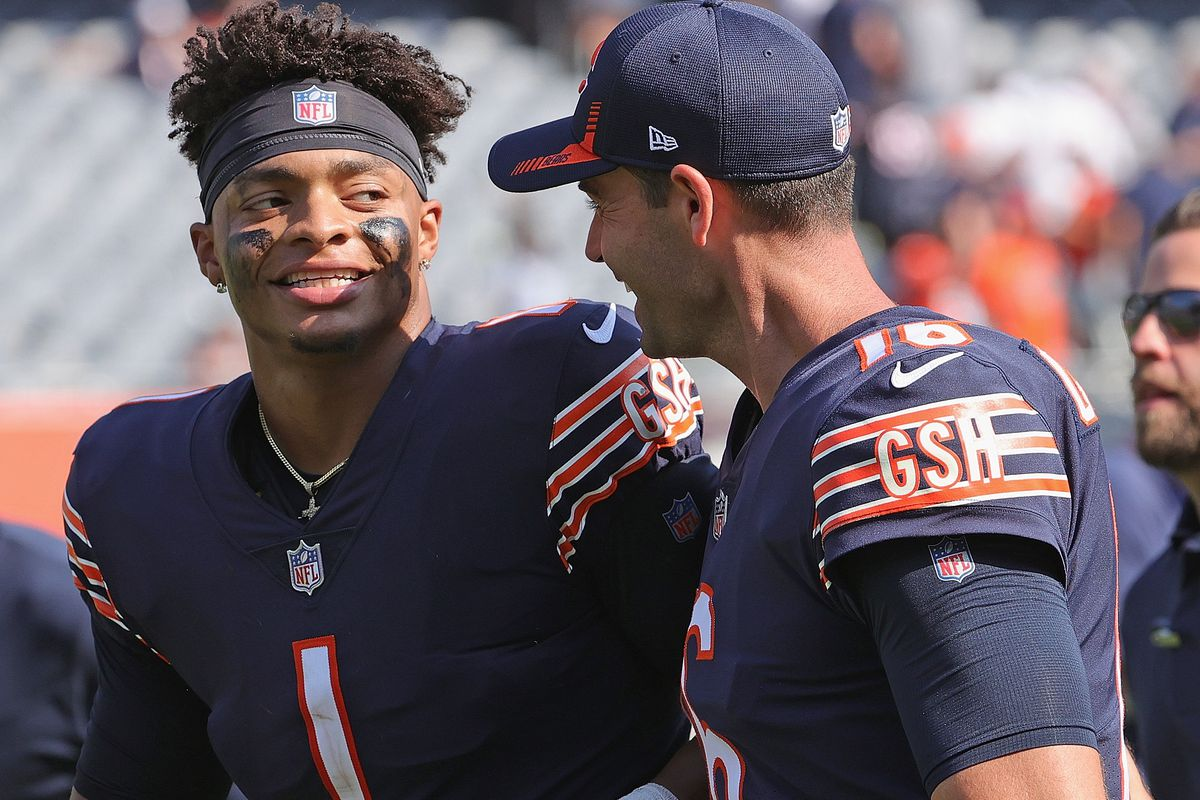Justin Fields #1 of the Chicago Bears smiles at Pat O'Donnell #16 as they leave the field following a win over the Cincinnati Bengals at Soldier Field on September 19, 2021 in Chicago, Illinois. The Bears defeated the Bengals 20-17.