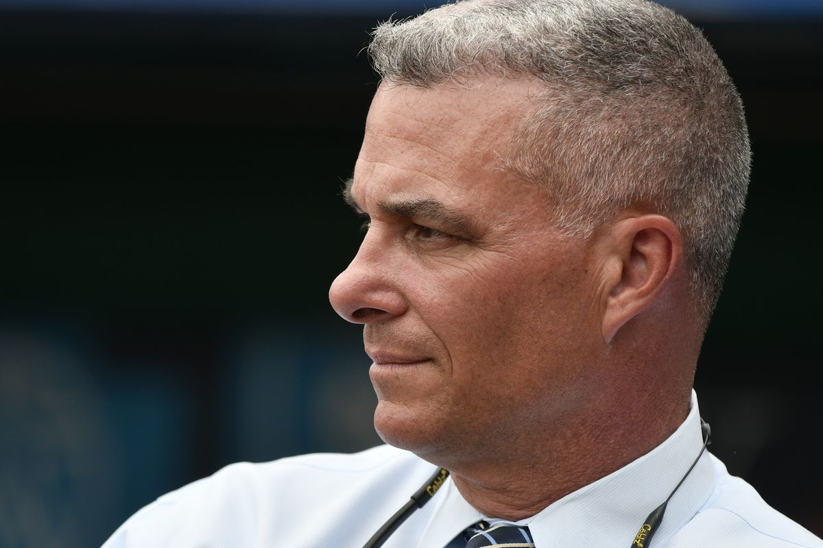 Dayton Moore looks at the product on the field he has constructed.