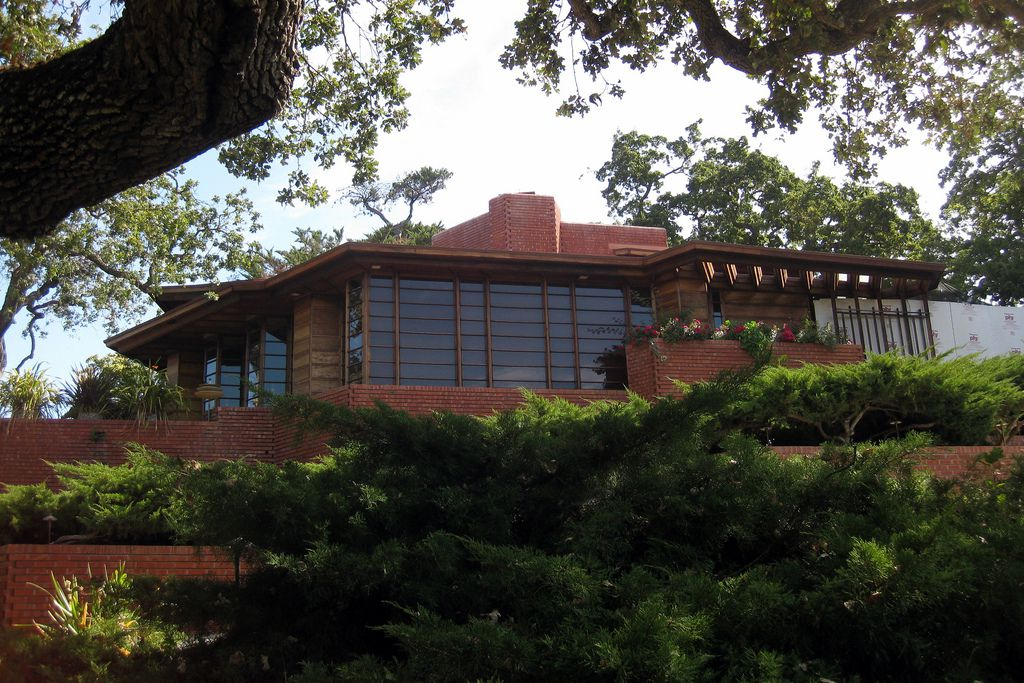The Hanna Honeycomb House by Frank Lloyd Wright. The house has a red brick facade with multiple windows. There are shrubs and trees surrounding the house.