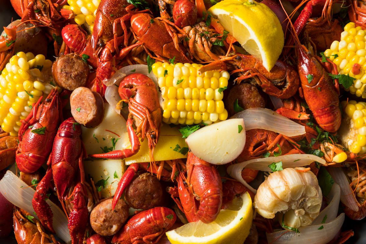 A mound of crawfish, with pieces of corn on the cob, potatoes, and lemon slices