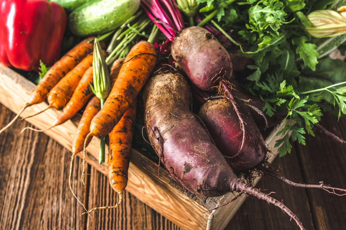 Carrots, potatoes, and other produce in a box.