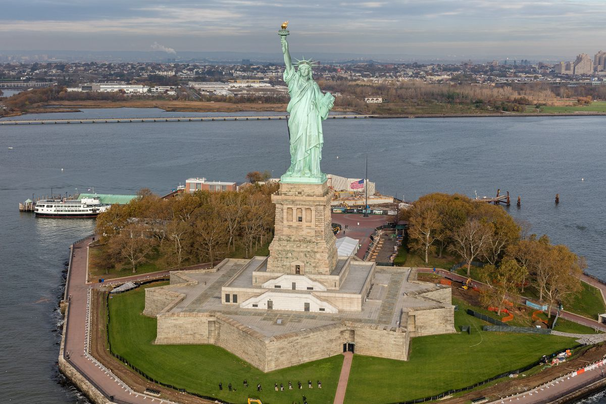 An island with the Statue of Liberty monument. The monument is of a woman wearing robes with a crown holding a torch.