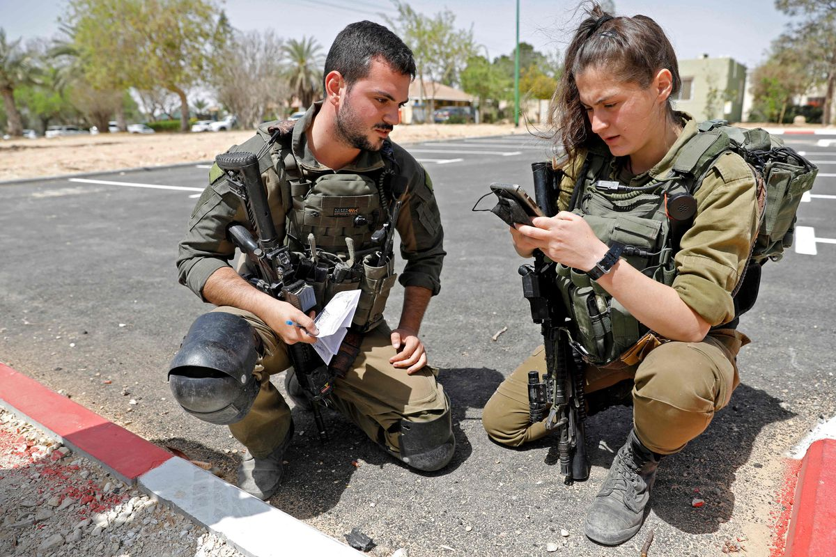 Israeli soldiers inspect a piece of debris after a missile launched from Syria landed in the vicinity of the Dimona nuclear site in Israel's southern Negev desert, on April 22, 2021.