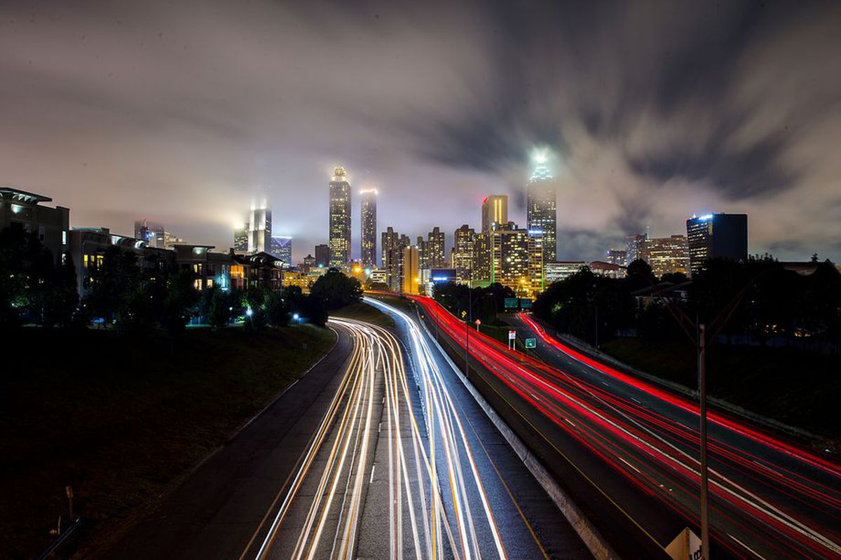 Traffic streams out of downtown Atlanta a night on a winding highway.