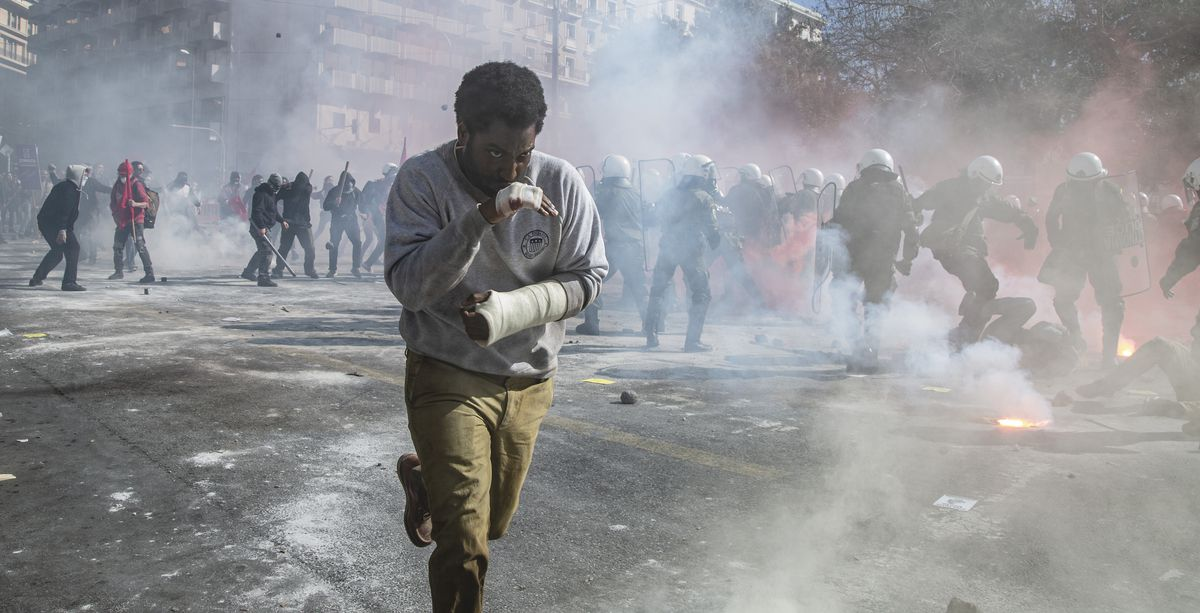 Beckett's protagonist John David Washington with his hands bandaged and bloodied, walks through smoky streets as a riot unfolds in the background