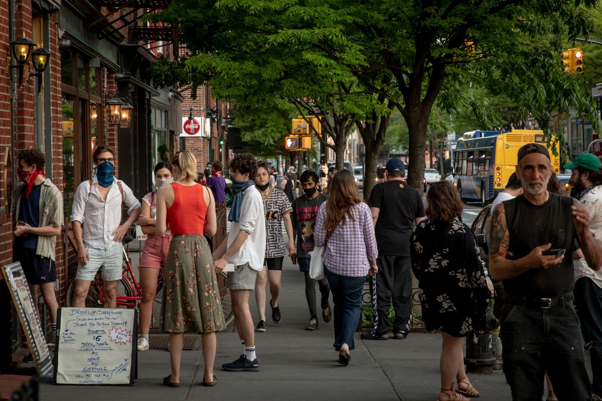 Groups of people gather outside of a bar's takeout window on a street in Greenpoint, Brooklyn