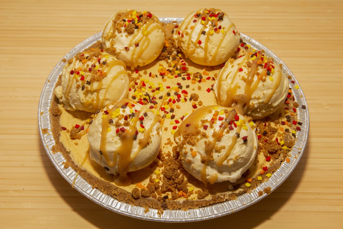 A dessert that looks like a pie topped with six scoops of ice cream, caramel sauce, and sprinkles