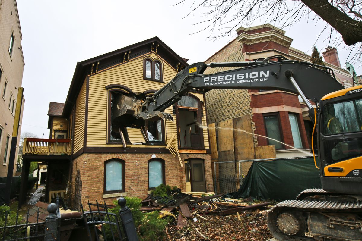 A two-story wood and brick house gets it's second story window torn out by a construction equipment.