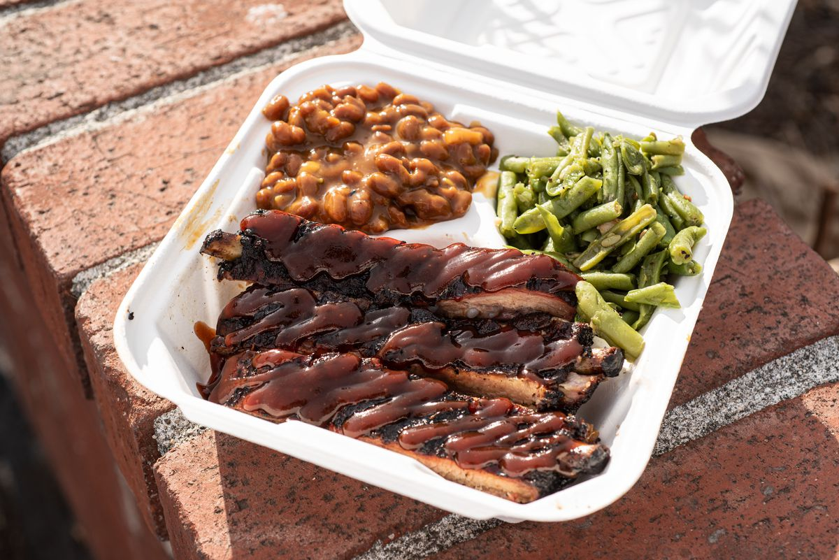 An order of pork ribs with baked beans and green beans.