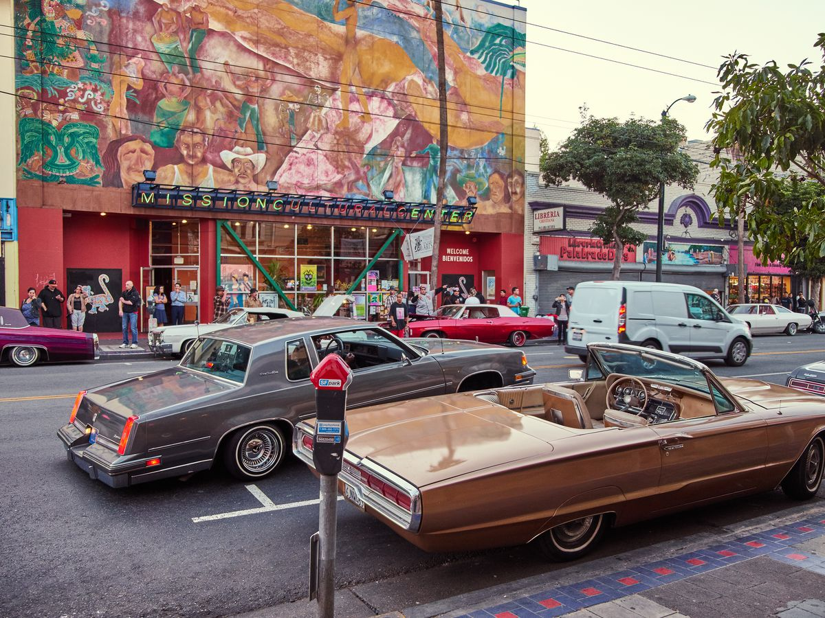 A street in the Mission District in San Francisco. There is a building with a colorful mural on one side of the street. Classic vintage cars are in the foreground.