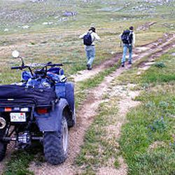 Two Forest Service rangers check on an ATV near Ennis, Mont. The Forest Service hopes education will stem a rash of illegal off-highway use.