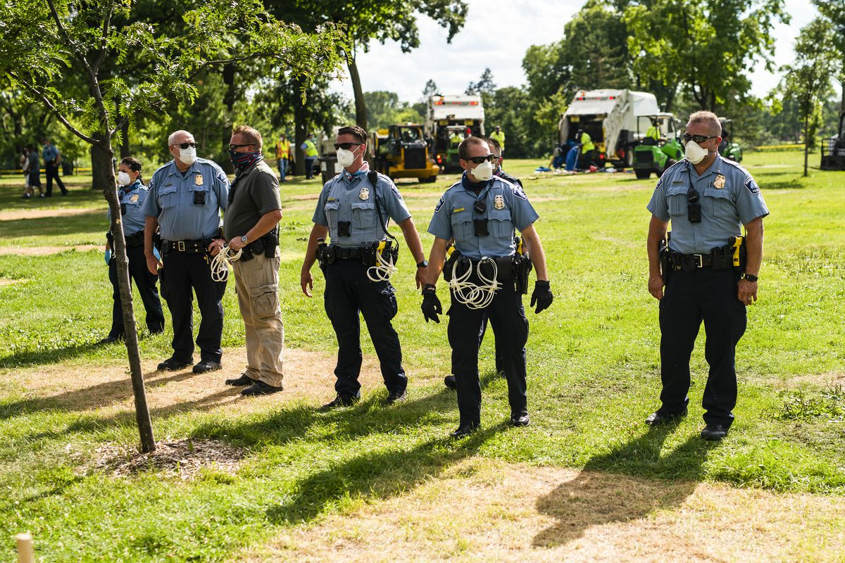 Six officers, all of whom appear to be white, stand in a park. They are wearing their blue and black uniforms, and are  masked, their belts heavy with zip tie handcuffs.