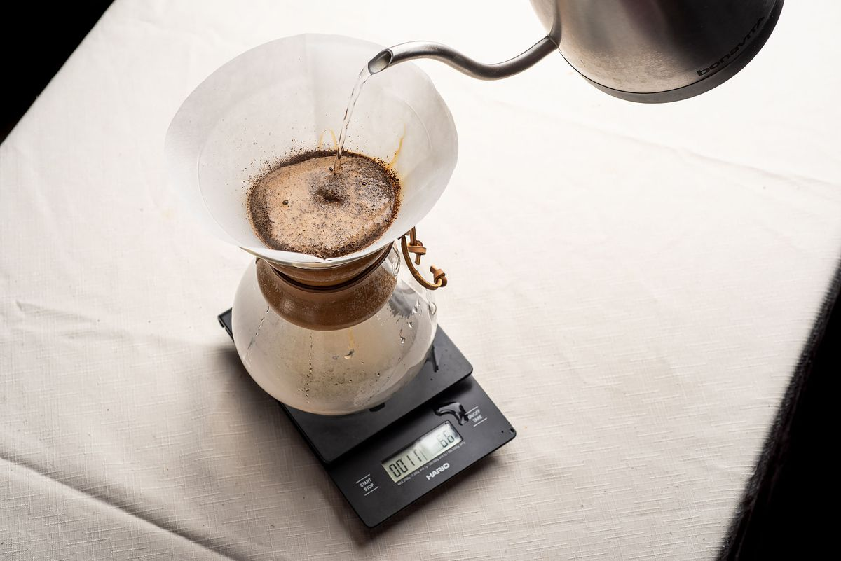 Hot water being poured from a kettle into the top of a Chemex, which is housing coffee grounds and a filter.