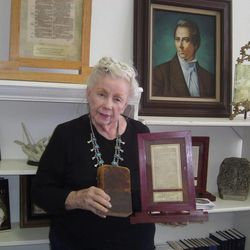 Helen Schlie holds her first-edition copy of the Book of Mormon and one of the framed pages from the book in her bookstore in Mesa, Ariz.