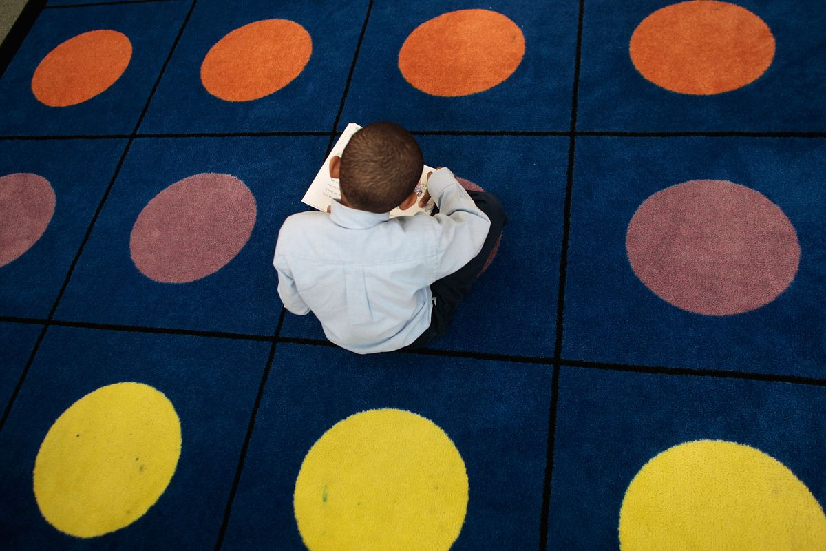 A student reads on a dotted carpet where students often sit for class at Harlem Success Academy.