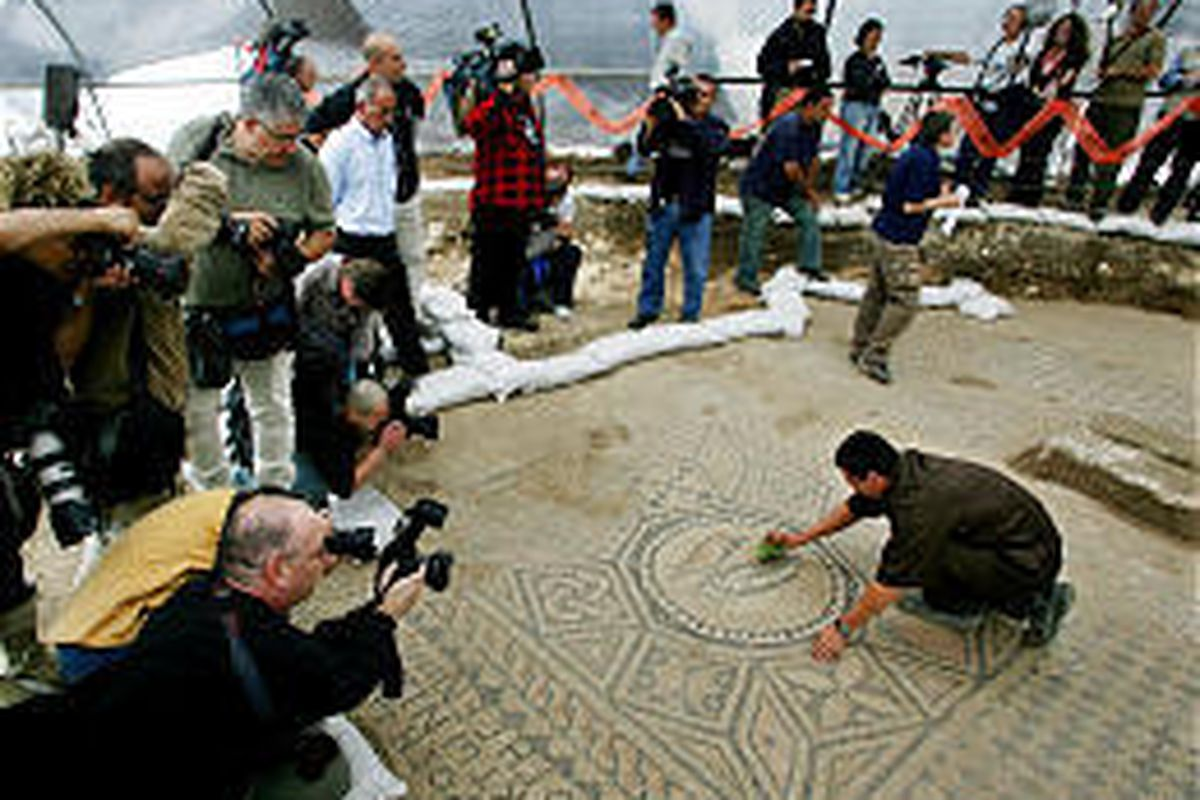 Surrounded by journalists, Israeli prisoner Ramil Razilo, right, cleans a section of a Christian mosaic floor in the Megiddo Prison.