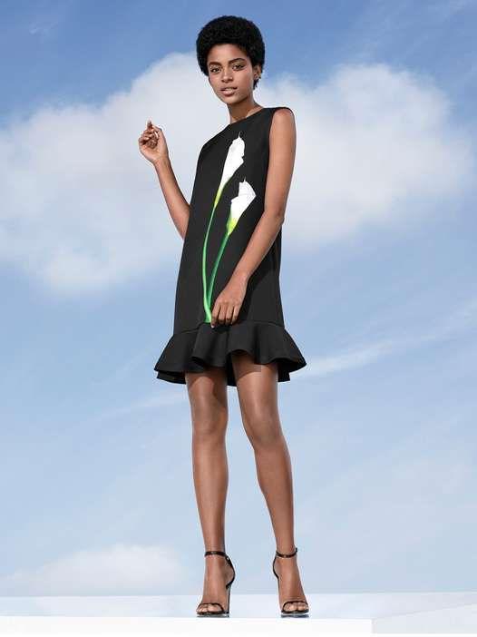 Model in black drop waist dress with floral design.