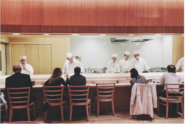 A handful of guests sit at a sushi counter, while multiple people in a white chef's outfit and hat work behind the counter