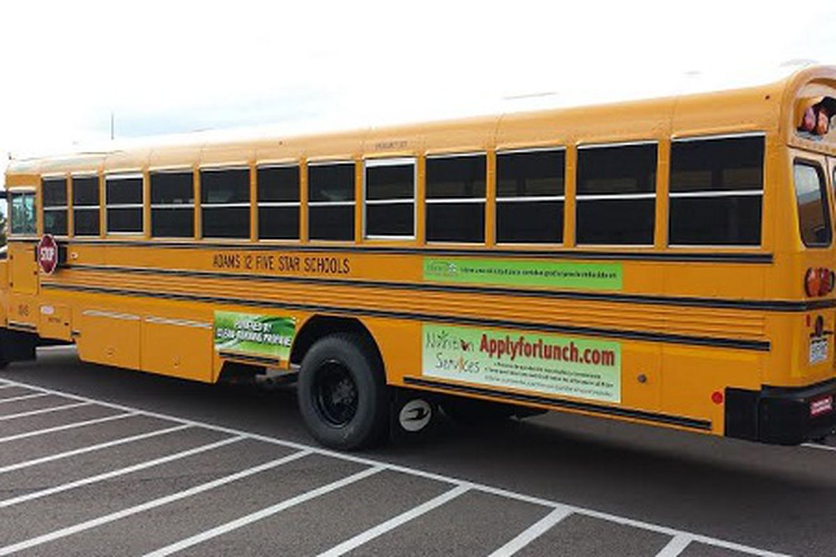 An Adams 12 school bus with an advertisement for the online application for free and reduced-price meals.