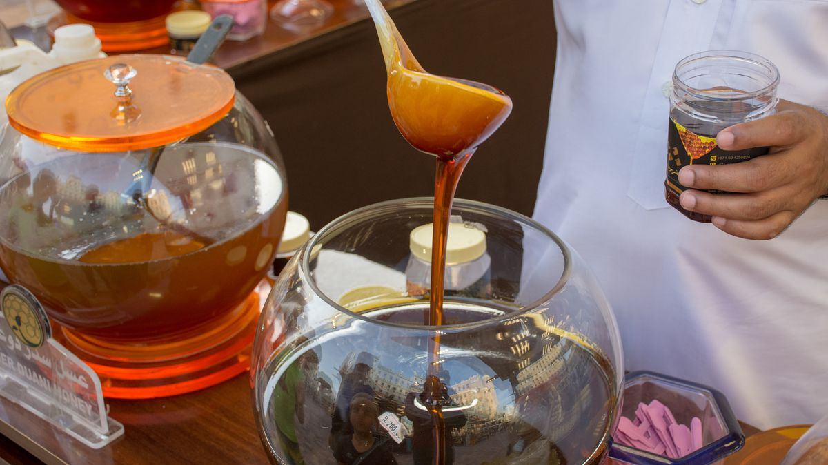 A man handles a ladle of dark honey. A bowl of light honey is to his side.