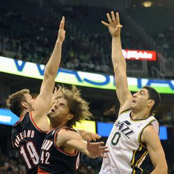 Utah Jazz center Enes Kanter (0) shoots over the defense of Portland Trail Blazers power forward Joel Freeland (19) and Portland Trail Blazers center Robin Lopez (42) in the second half of a game at the Energy Solutions Arena on Wednesday, October 16, 2013.