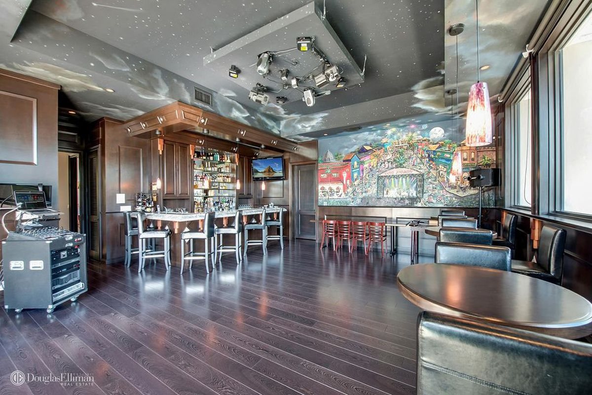Inside the nightclub room at 12991 Lerida Street in Coral Gables with a bar, raised seating, disco lights, and more