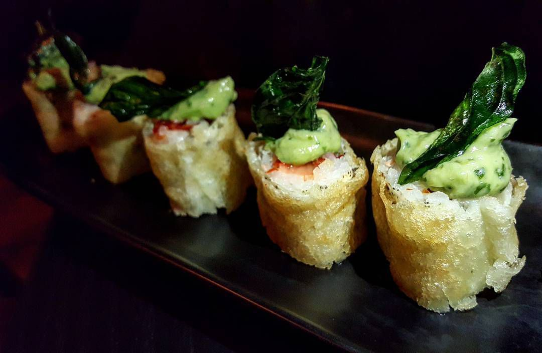 Sushi rolls wrapped in a crispy skin and topped with a thick green sauce sit on a long black plate