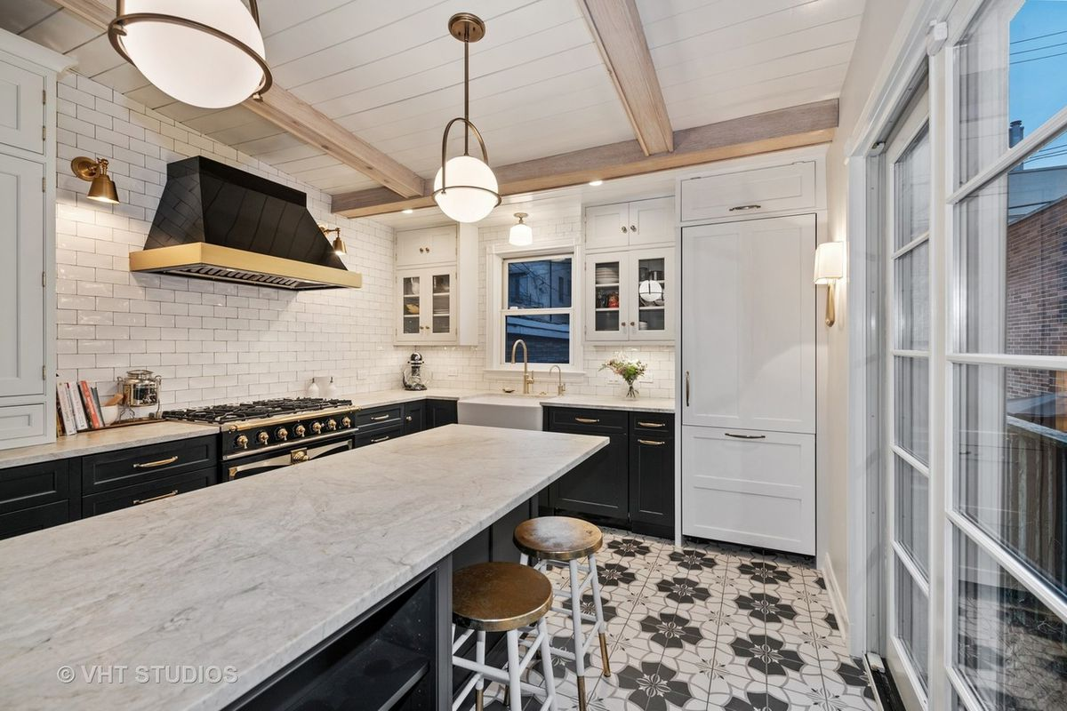 A kitchen with a large island, navy cabinets, white tile backsplash, and gold light fixtures.