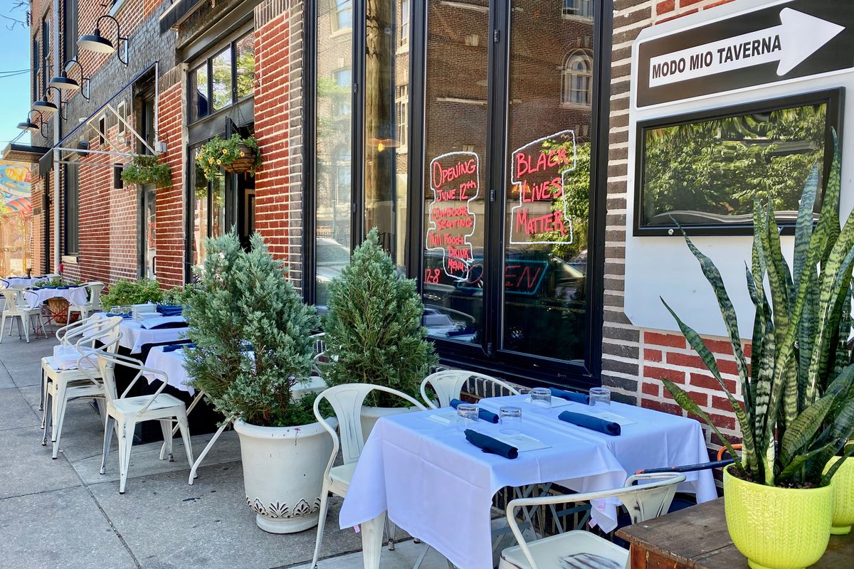 outdoor tables at a restaurant with sign that says modo mio taverna and sign says black lives matter