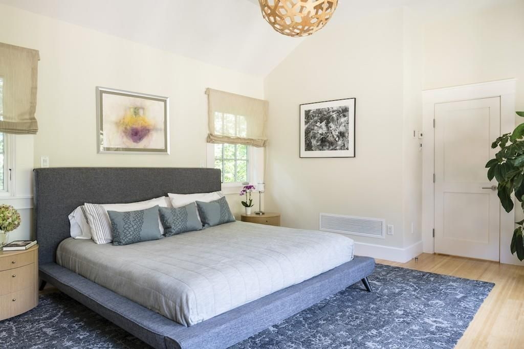 A bedroom with a large bed and a hanging spherical light.