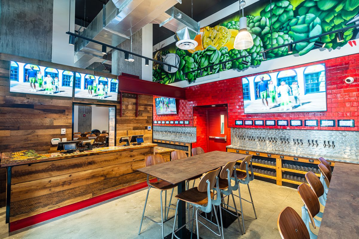 Tap99's space includes red brick walls, TVs, a wood-lined ordering area, and a mural of green hops.