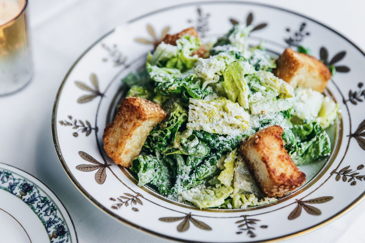 A plate of salad greens with four large croutons, sprinkled with parmesan cheese.