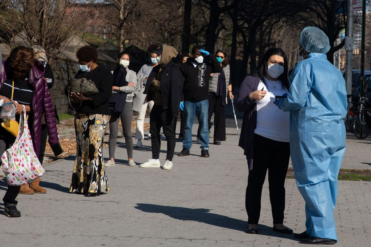 People wait to be pre-screened for the coronavirus outside the Brooklyn Hospital Center.